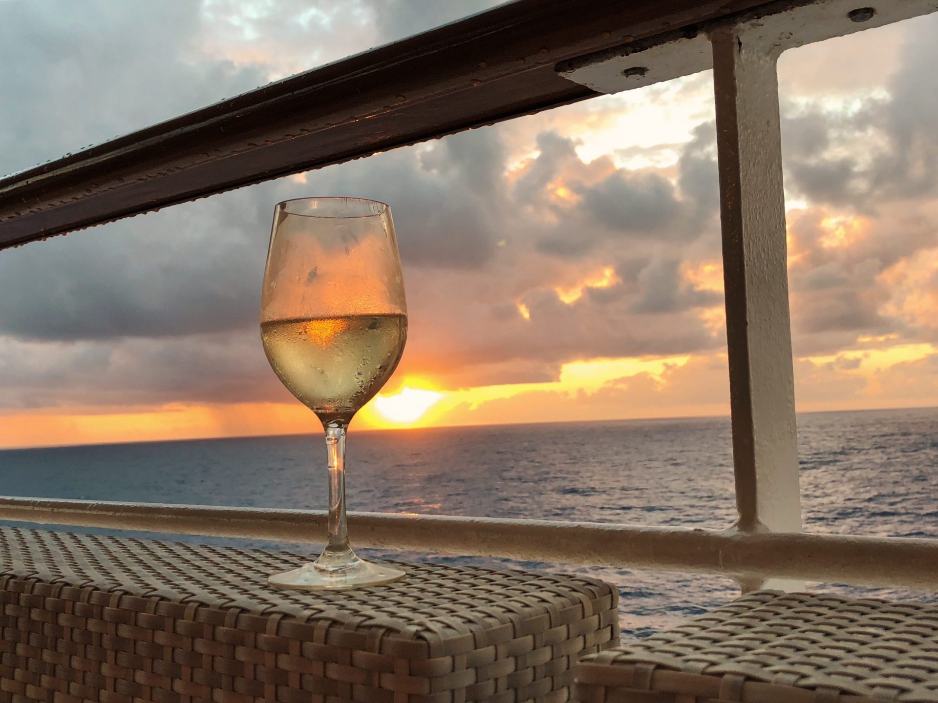 Enjoying a cold glass of white wine in your luxury yacht by the sea during a beautiful sunset | Luxury Homes by Brittany Corporation