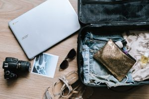 Flat lay of travel essentials including a laptop, a camera, sandals, sunglasses, a polaroid, and a bag full of clothes and personal accessories | Luxury Homes by Brittany Corporation