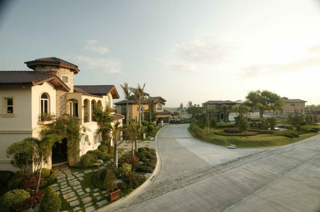 Warm summer day in Italian inspired themed community of yellows and oranges, and cobblestone designed roads and old classic lamp posts, and a lush green courtyard of small hedges with a water fountain in the center | Luxury Homes by Brittany Corporation