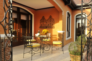 The veranda with a dining table and chairs perfect for safe and socially-distanced gatherings with small groups of friends in your orange-themed Italian luxury house | Luxury Homes by Brittany Corporation