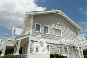 Statues of angels in front of a gray Old American-themed luxury house at Georgia Club | Brittany Sta. Rosa | Luxury Homes by Brittany Corporation