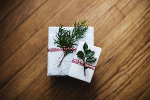 Presents wrapped in white wrapping paper and mistletoe   Luxury Homes by Brittany Corporation