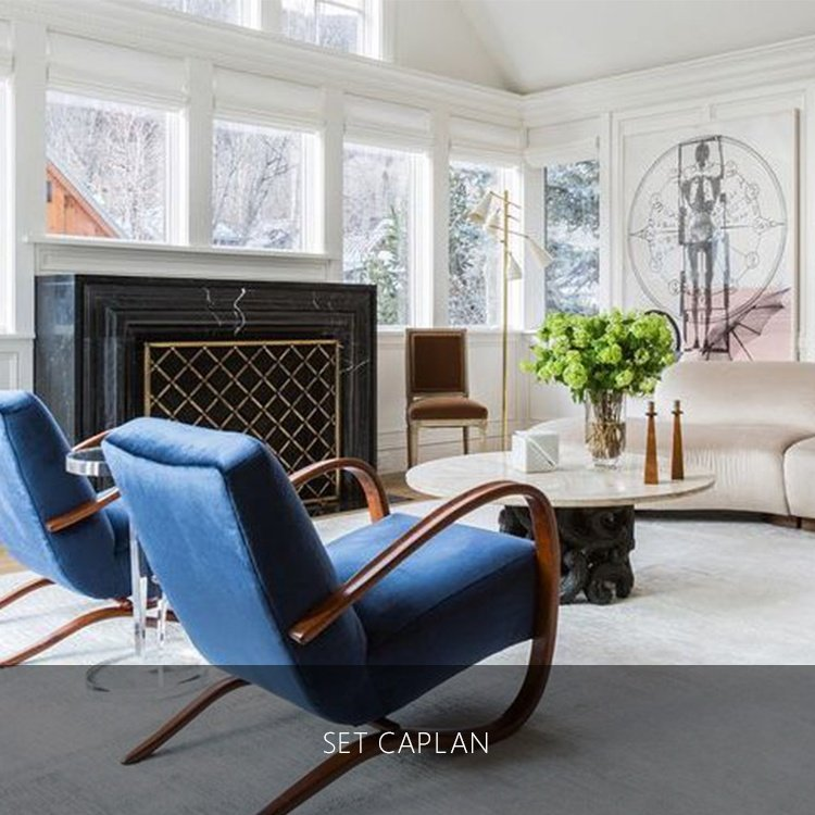 two blue chairs in front of a fire place and marble table with a painting of a skeleton in a luxury house | Luxury homes by brittany corporation