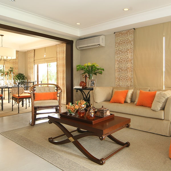 A luxury house's living room filled with beige furniture with orange accents | Luxury Homes by Brittany Corporation