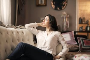 A young caucasian woman with brown hair relaxing on her Victorian-inspired couch in the living room of her luxury house | Luxury Homes by Brittany Corporation