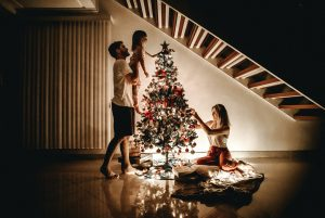 A young white family of three decorating their small Christmas tree in their luxury house   Luxury Homes by Brittany Corporation
