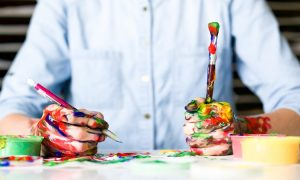 An artist with hands covered in paint while creating photo murals | Luxury Homes by Brittany Corporation