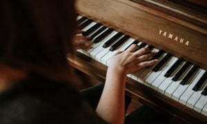 Over the shoulder picture of a woman practicing her hobby at home by playing the piano on her Yamaha wooden grand piano | Luxury Homes by Brittany Corporation
