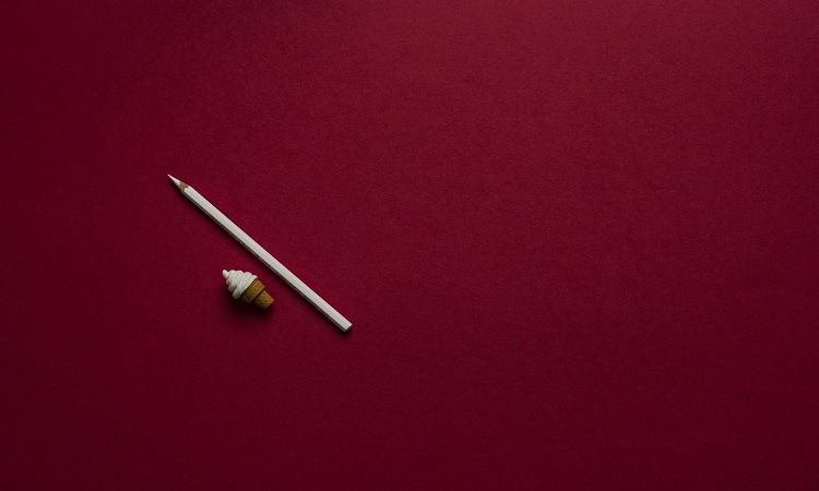 Miniature ice cream figure and white color pencil on a flat maroon background | Luxury Homes by Brittany Corporation