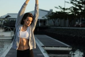 Young Caucasian woman in white sports bra, grey jacket, and black pants stretching her arms after her morning workout in her luxury themed community | Luxury Homes by Brittany Corporation