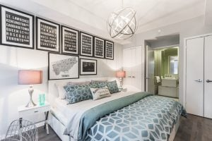 Low wide angle shot of a small bedroom with unique and colorful patterns on the wall, the rug, and the bedsheets | Luxury Homes by Brittany Corporation