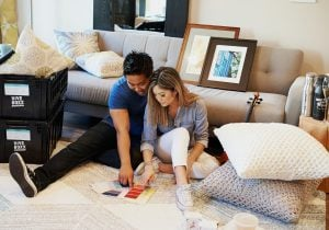 Young artistic asian couple picking colors from a color sampler for the furniture in their newly moved into luxury house | Luxury Homes by Brittany Corporation