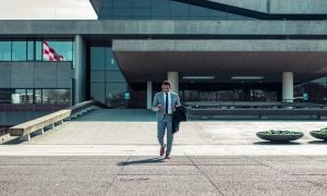 Young caucasian professional with a mixed ethnic background in a grey suit using his phone while stepping out of his office building | Luxury Homes by Brittany