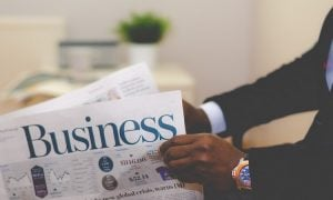 An African-American man in a black suit with a blue watch reading the Business section of the newspaper | Luxury Homes by Brittany Corporation