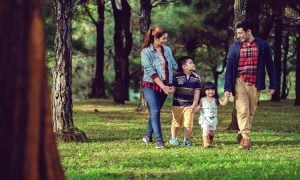 A young family of four enjoying a stroll through the lush green pine trees at Crosswinds Tagaytay | Luxury Homes by Brittany Corporation
