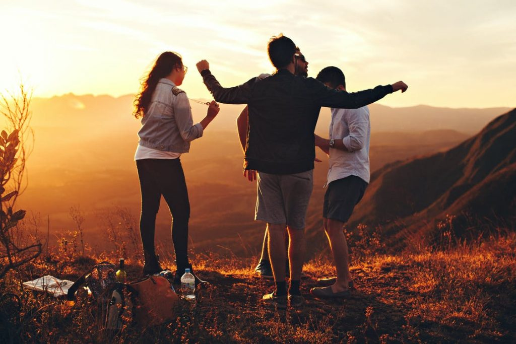 A group of 4 friends enjoying a cool summer getaway in the mountains with warm sunset views.