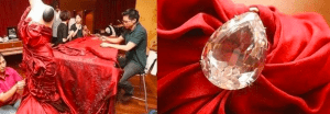 A picture divided into 2 separate images; on the left, a silk chiffon scarlet red draped dress with four asian malaysian workers weaving or sewing small diamonds into the dress on a long table inside a spacious brown studio room; on the right is a zoom in image of a pear cut or pear shape sparkling diamond sewed into the dress and reflecting the light in every edge