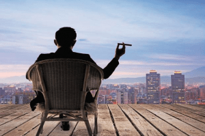 Wealth man sitting on the roof of his luxury home looking at the city - Luxury homes by Brittany