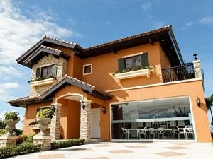 Orange Italian inspired classic luxury house with transparent glass area showing a modern office, and an unroofed garage | Vista Alabang | Luxury Homes by Brittany Corporation