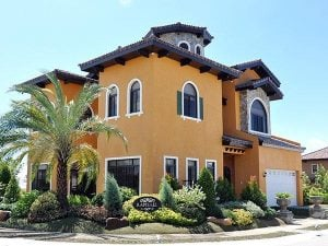 Tall orange Italian classic mansion with front garden and palm trees | Luxury Homes by Brittany Corporation