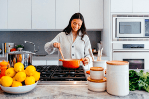 Girl cooking breakfast in the spacious kitchen of her luxury home, luxuries in the new normal | Luxury Homes by Brittany Corporation