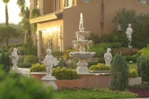 Portofino Heights community shot of rotunda with fountain and statue decors with vibrant greenery that complements the luxury house and lot for sale developments - Luxury Homes by Brittany