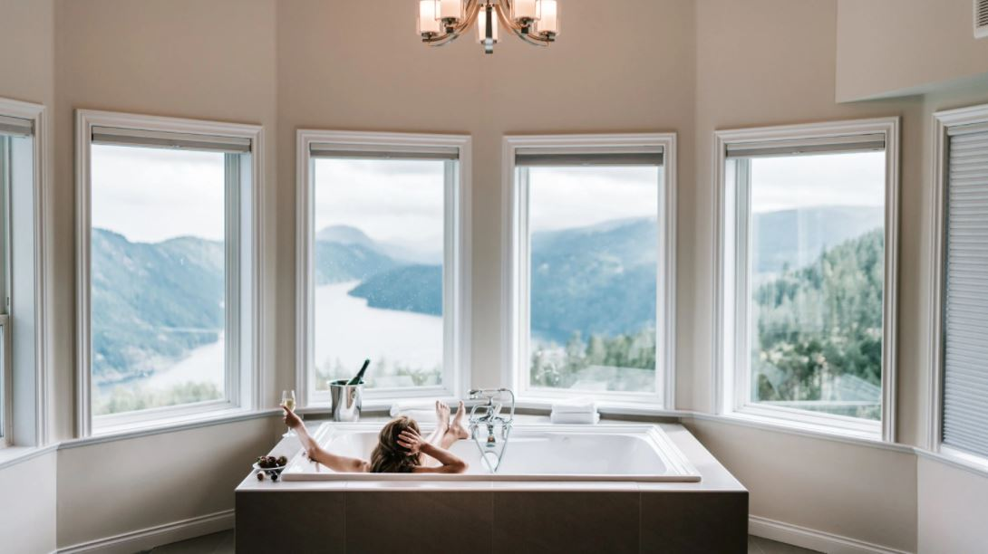 Woman practicing best skin care tips with a luxury home spa experience in a bathtub with a grand view at Brittany Corporation
