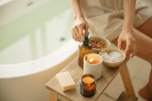 Woman sitting on a bathtub with tray of candles, bath salts, lotion, and soap, a luxury home spa experience at Brittany Corporation