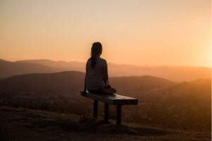 Woman practicing self-care by sitting on a bench and watching the sunset view above mountaintop scenery- Luxury homes by Brittany