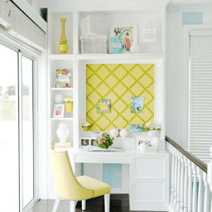 The unique architecture of a home office nook with a desk, comfortable chair, yellow wall board, and decorations | Luxury Homes by Brittany Corporation