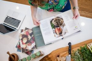 Top view of light skinned brunette woman wearing tropical colors, reading through books on plant-based diets on a white counter with healthy ingredients and a chopping board and a macbook laptop, in a kitchen | Luxury Homes by Brittany Corporation