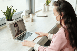 Caucasian brunette female in her twenties wearing a pink button down shirt and a face mask, video calling an Asian male wearing a face mask, through her macbook laptop, on a windowside wooden desk with pots of succulent plants and home decoration | Luxury Homes by Brittany Corporation