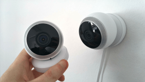 ight skinned hand installing two round home security cameras or CCTV that are color white and have built in mics | Luxury Homes by Brittany Corporation