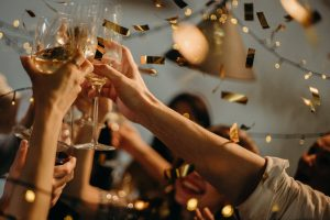 A group of young people celebrating a birthday by raising a toast with champagne | Luxury Homes by Brittany Corporation