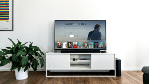 Flat screen TV previewing Gone Girl movie on a white desk table, next to a potted leafy green plant, in a modern minimalist white living room with dark wooden flooring | Luxury Homes by Brittany Corporation