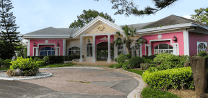 Pink Southern American style club house by a paved rotunda with healthy green pine trees, palm trees, and bushes | Georgia Club Sta Rosa | Luxury Homes by Brittany Corporation
