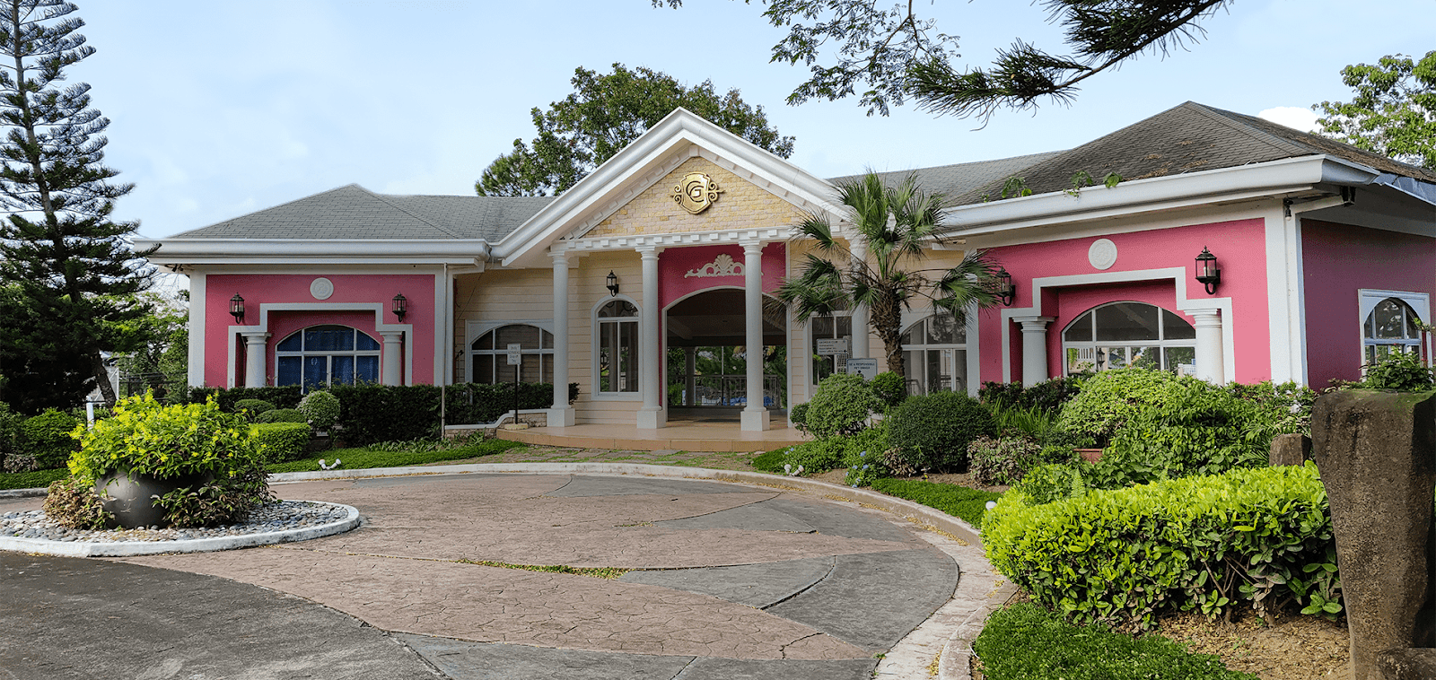 Pink Southern American style club house by a paved rotunda with healthy green pine trees, palm trees, and bushes | Luxury Homes by Brittany Corporation