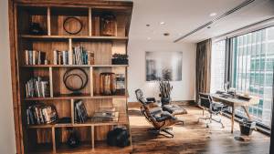 Spacious office on a high floor in a building, with a wooden corner shelf of books and ornaments, a leather recliner armchair, a wall painting, a potted green snake plant, a leather computer chair together with a wooden desk against the glass wall overlooking a view from high up | Luxury Homes by Brittany Corporation