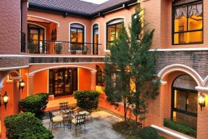 Interior of an orange Italian mansion showing two floors and an open courtyard with trees, bushes, and a breakfast dining area or lanai on stone tiles | Luxury Homes by Brittany Corporation