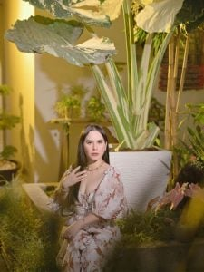 Elegantly dressed long black haired and fair skinned woman Jinkee Pacquaio, wife of Manny Pacquiao, in a living room surrounded by leafy green indoor expensive house plants of all sizes | Luxury Homes by Brittany Corporation