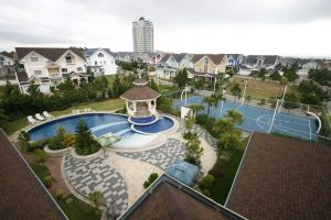 Panoramic view of a village or subdivision property showing dainty colorful houses and mansions; and amenities such as a swimming pool, clubhouse, basketball court, open space grassy park, and gazebo | Luxury Homes by Brittany Corporation