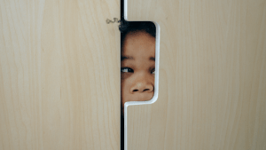 Dark skinned young little girl with curly black hair hiding in a light colored wooden cabinet | Luxury Homes by Brittany Corporation