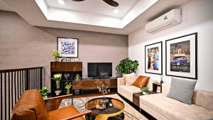 Upper floor living room with orange leather armchair and two cream color suede couches with patterned couch pillows, a golden round coffee table on a thick abstract carpet, a flatscreen TV on a sleek table, plants in a sleek shelf, and framed abstract artworks on white walls | Luxury Homes by Brittany Corporation
