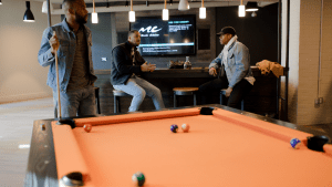 Three black men in hip and casual attire drinking whiskey in an indoor bar and playing billiards on an orange pool table, while music is playing and flashed on a flat screen TV installed on the wooden wall, with two speakers on both sides | Luxury Homes by Brittany Corporation