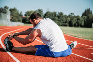 Western brunette man with facial hair and a muscular body, stretching his leg on the floor in a running track | Luxury Homes by Brittany Corporation