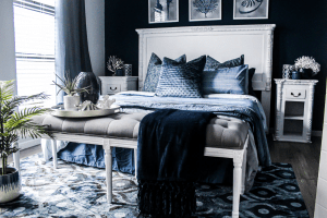 Blue themed bedroom with a queen size bed of comfortable sheets and pillows, on a patterned rug on the wooden floor perfect for fixing your sleeping habits | Luxury Homes by Brittany Corporation