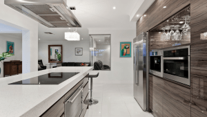 Spacious white sleek and modern kitchen with built in ovens, upside-down wine glass holder, and touchscreen stove on the counter, overlooking other areas in the house | Luxury Homes by Brittany Corporation