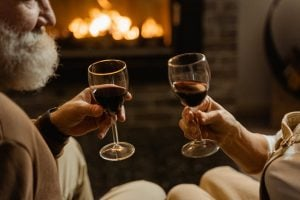 An old couple enjoying the best wine by the fireplace of their luxury home in Tagaytay | Luxury Homes by Brittany Corporation