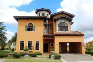Orange Italian ready-for-occupancy mansion with a brick tower; a front garden with palm trees, bushes, and potted ferns; an open garage or carport; under a cloudy blue sky   Luxury Homes by Brittany Corporation