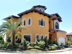 Italian Orange mansion with a brick tower; a front garden with palm trees, bushes, and potted ferns; an gated garage or carport; under a clear blue sky | Luxury Homes by Brittany Corporation